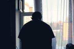 Mannen på fönstret som böjer hans huvud ner i fördjupning, önskar att begå självmord arkivbilder