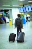 Mannen på flygplatsen med en resväska royaltyfri bild