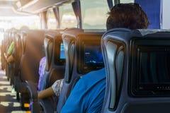 Mannen på passagerareplatsen av bussen lyssnar till musik och ser minnestavlan Han ser skärmen för apparat` s och ler Royaltyfria Bilder