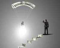 Mannen på pengartrappa som ser den ljusa kulan med pengar, hoppa fallskärm Arkivbilder