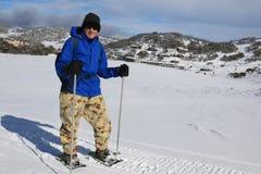 Mannen på snö skor resande över snö på Smiggin hål, den Kosciuszko nationalparken NSW Australien Arkivbild