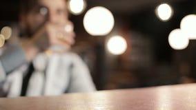 Mannen på stången dricker whisky Närbild Glider ett exponeringsglas över stången och slår handen lager videofilmer