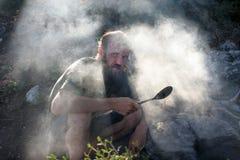 Mannen på vilar med en stor sked på branden Arkivfoton