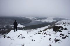 Mannen på toppmötet som ser in mot snö, täckte dalen Royaltyfri Foto