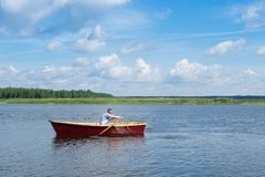 Mannen paddlar i ett träfartyg, bad på sjön på en solig dag, aktiv helg arkivbilder