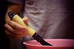 Mannen piskar smeten med en vifta Matlagning bakning, mål Arkivbild