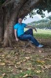 Mannen poserar yttersidan i parkera Royaltyfri Fotografi