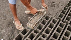 Mannen producerar manuellt tegelstenformer för konstruktion från den vulkaniska askaen i staden av Legazpi philippines lager videofilmer