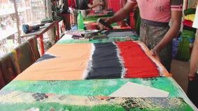 Mannen producerar stämpeltrycktorkduken på seminariet på den nya marknaden i Dhaka, Bangladesh lager videofilmer