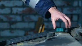 Mannen räcker att kontrollera bilen den olje- nivån inom garaget 4K arkivfilmer
