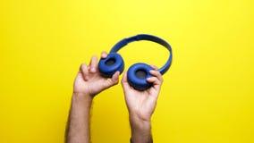Mannen räcker att rymma blåa hörlurar med mikrofon i hans händer stock video