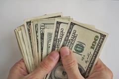 Mannen räcker att rymma och att räkna högen av amerikansk valuta för US dollar, USD som symbol av affärsframgång Royaltyfri Fotografi