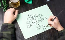 Mannen räcker att skriva ett lyckligt St Patrick dagkort Arkivfoton