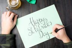 Mannen räcker att skriva ett lyckligt St Patrick dagkort Royaltyfri Fotografi