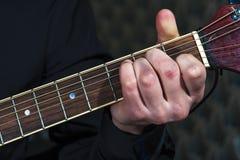 Mannen räcker att spela på den akustiska gitarren, closeup Royaltyfria Foton