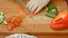 Mannen räcker bitande röd peppar för sallad Arkivbilder