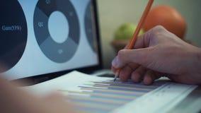 Mannen räcker danandeanmärkningen med blyertspennan på utskrivavna analyserande grafer lager videofilmer