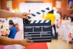 Mannen räcker den hållande filmclapperen Begrepp för filmdirektör Fotografering för Bildbyråer