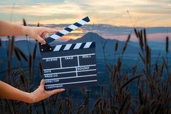 Mannen räcker den hållande filmclapperen Begrepp för filmdirektör royaltyfri foto