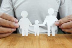 Mannen räcker den hållande vitbokfamiljen Arkivbild