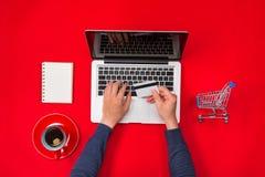 Mannen räcker framställning av en betalning genom att använda en kreditkort, online-shopping royaltyfri bild