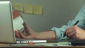 Mannen räcker genom att använda den grafiska minnestavlan som skapar byggprojekt på bärbara datorn stock video