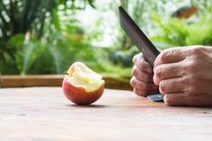 Mannen räcker genom att använda minnestavladatoren och det bet äpplet på trätabl Royaltyfri Fotografi