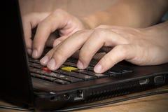 Mannen räcker maskinskrivning på bärbara datorn Arkivfoto
