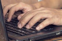 Mannen räcker maskinskrivning på bärbara datorn Arkivbild