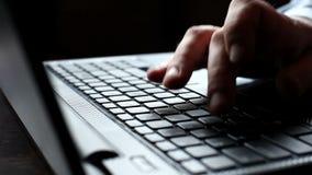 Mannen räcker maskinskrivning på ett bärbar datortangentbord arkivfilmer