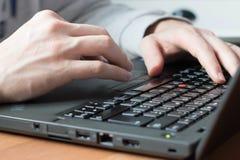 Mannen räcker maskinskrivning på ett datortangentbord arkivbild