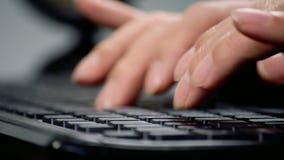 Mannen räcker maskinskrivning på ett datortangentbord arkivfilmer