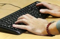 Mannen räcker maskinskrivning på ett tangentbord Royaltyfri Fotografi