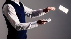Mannen räcker tärande pengar, kassa, dollar Manhänder i formella kläder som kastar pengar på grå bakgrund royaltyfria foton