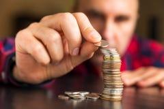 Mannen räknar hans mynt på en tabell Arkivfoto