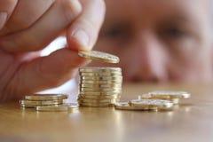 Mannen räknar hans mynt på en tabell Närbild av handen som sätter ett mynt till bunten av guld- mynt Royaltyfri Foto
