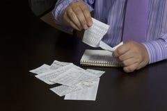 Mannen räknar kostnaden av kontanta checkar En familjbudget arkivfoton