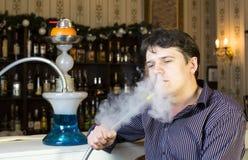 Mannen röker en vattenpipa Arkivfoto