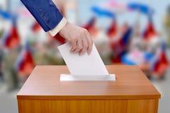Mannen röstar, genom att kasta en sluten omröstning i valurnan royaltyfria bilder
