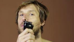 Mannen rakar hans framsida, stort skägg med rakapparatnärbild lager videofilmer