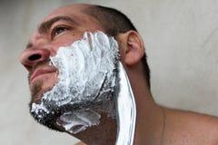 Mannen rakar hans skägg med en kniv arkivbild