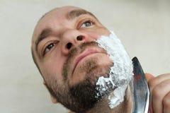 Mannen rakar hans skägg med en kniv royaltyfri bild