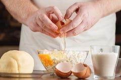 Mannen räcker avbrott av ägg in i en bunke; closeup Arkivfoto