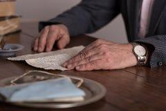 Mannen räcker den hållande gamla bokstaven Arkivfoton