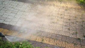Mannen rengöringsmedel, tvättar kullersten med en stråle av högtryckvatten, närbild lager videofilmer