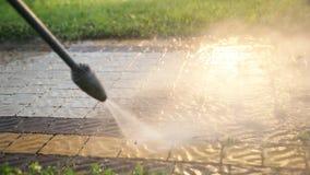 Mannen rengöringsmedel, tvättar kullersten med en stråle av högtryckvatten, närbild arkivfilmer