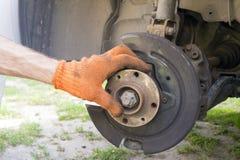 Mannen reparerar den främre suspenderen av en bil royaltyfri foto
