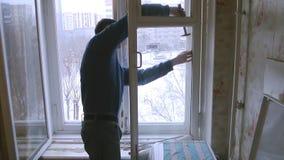 Mannen reparerar det wood fönstret Byt ut brutet exponeringsglas på fönster arkivfilmer