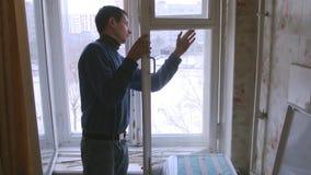 Mannen reparerar det wood fönstret Byt ut brutet exponeringsglas på fönster stock video