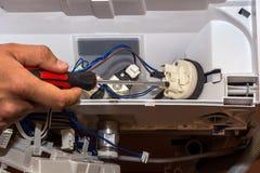 Mannen reparerar elektroniken av tvagningmaskinen fotografering för bildbyråer